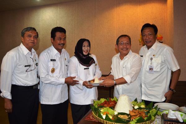 Ketua DPRD Gresik A Hamid memberikan potongan tumpeng Kepada Kepala DPPKAD Gresik, Dr. Yetty Sri Suparyatie. (foto: Humas Pemkab Gresik)