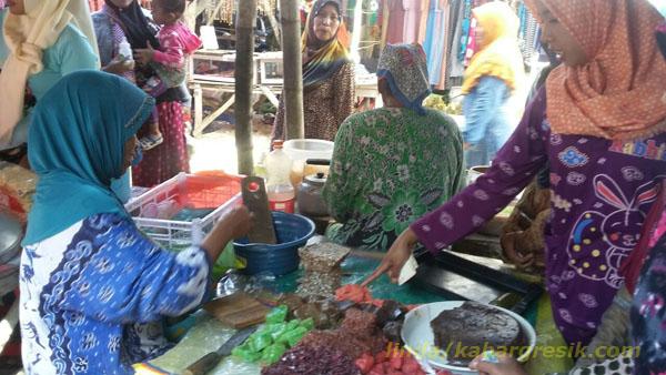 Asyarotun sedang melayani pembeli jajan tradisional di Pasar Tirem Enggal Dukun Gresik. (Foto: Linda/mg2/kabargresik.com)